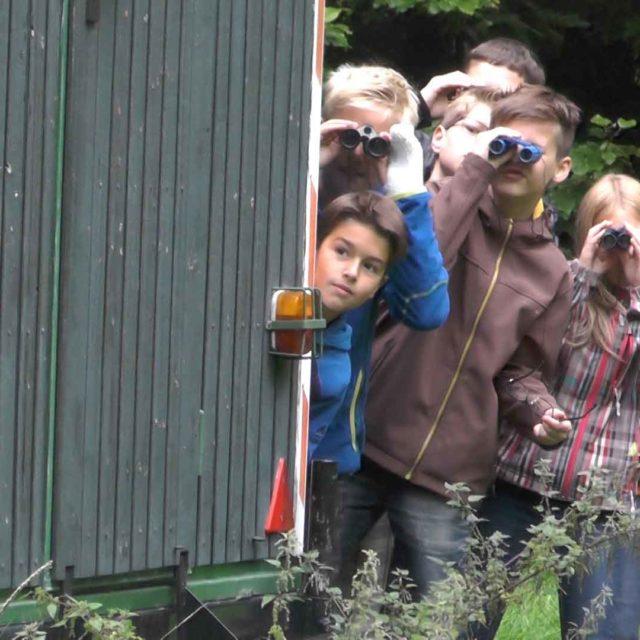 Kinderbande schaut mit Ferngläsern hinter Bauwagen hervor