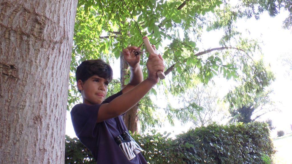 Junge schießt Steinschleuder