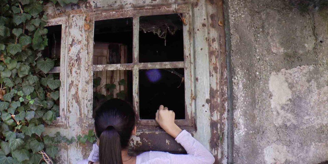 Mädchen leuchtet mit Taschenlampe in verlassenes Haus
