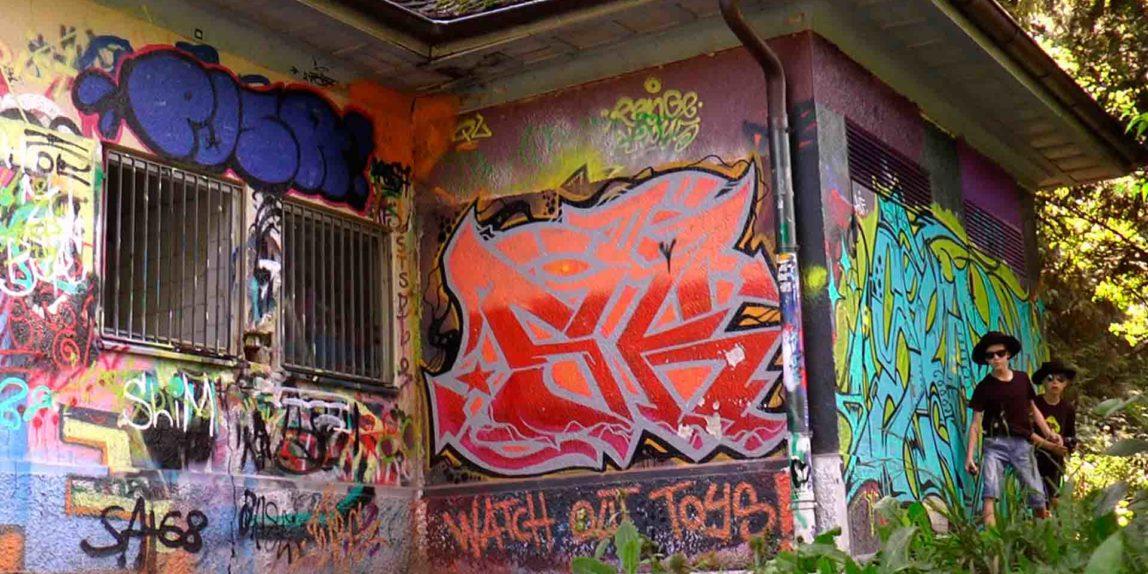Gangster schleichen an Grafitti-Wand entlang